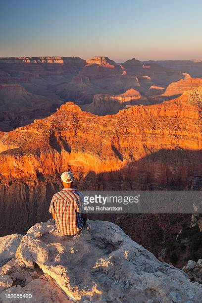 A man sitting on a rock outcrop looking at the view of a desert canyon landscape.