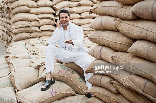 Man sitting on a sack of wheat and talking on a mobile phone, Anaj Mandi, Sohna, Gurgaon, Haryana, India