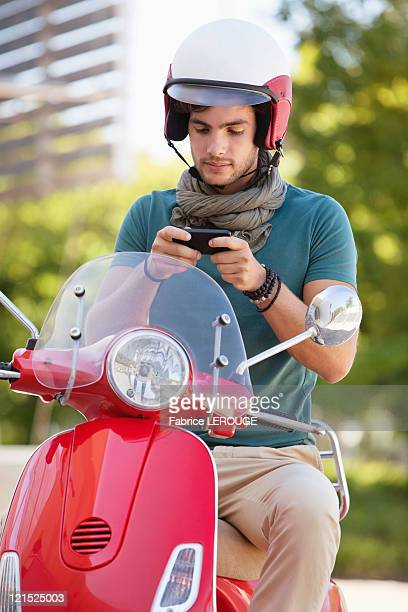 Man sitting on a scooter and text messaging