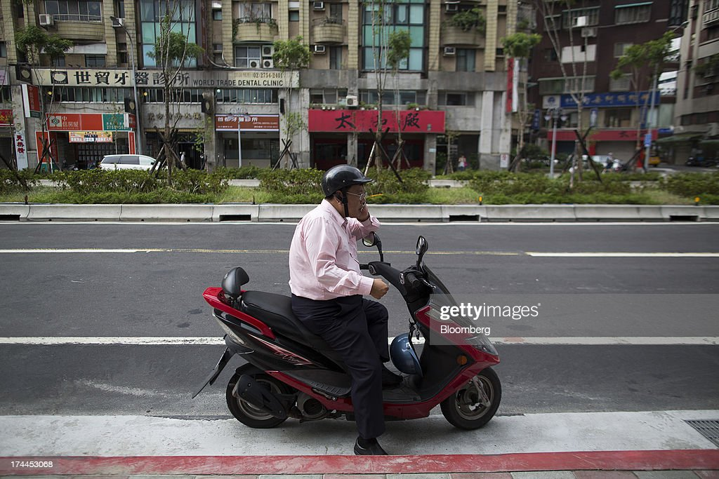 A man sitting on a scooter talks on a mobile phone on Hsin Yi Road in Taipei, Taiwan, on Wednesday, July 24, 2013. Taiwan President Ma Ying-jeou ruled out driving down the Taiwan dollar to boost exports following the currencys rally against the yen and said the government still aims for growth of at least 2 percent this year. Photographer: Jerome Favre/Bloomberg via Getty Images