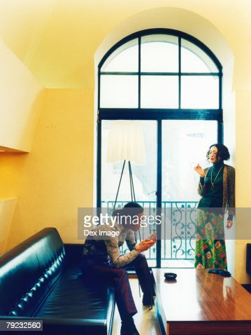 Man sitting on a sofa, woman standing against wall, smoking cigarettes : Stock Photo