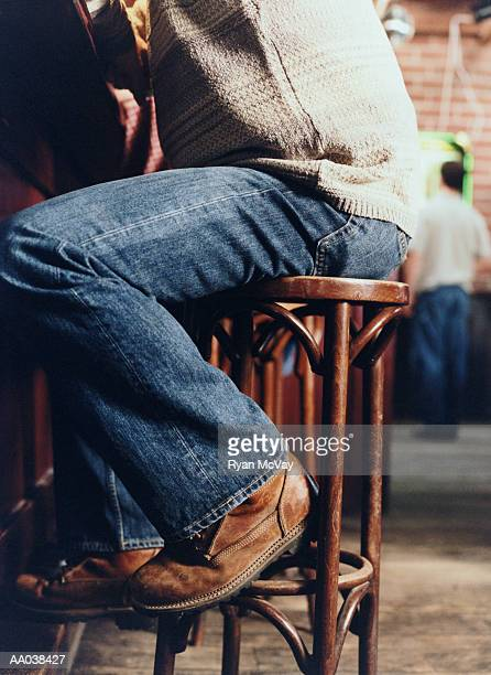 Man Sitting on a Stool at a Bar