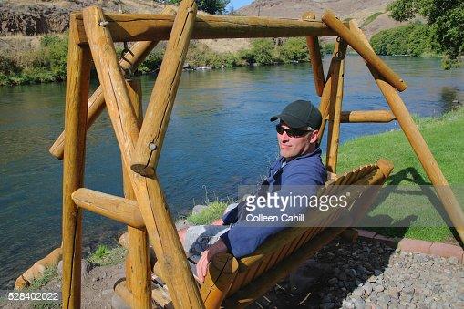 A Man Sitting On A Swing At The Water's Edge; Maupin Oregon United States Of America