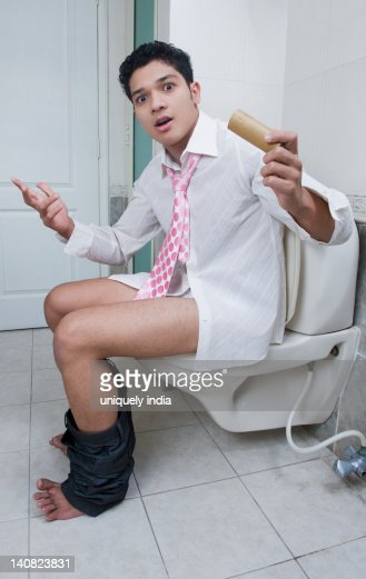 Man Sitting On A Toilet And Gesturing Stock Photo | Getty ...