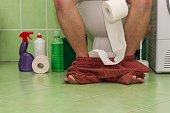 Man sitting on a toilet in a family house. Abdominal pain. Diarrhea