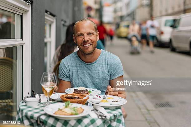 Man sitting on a walkway cafe on summer day