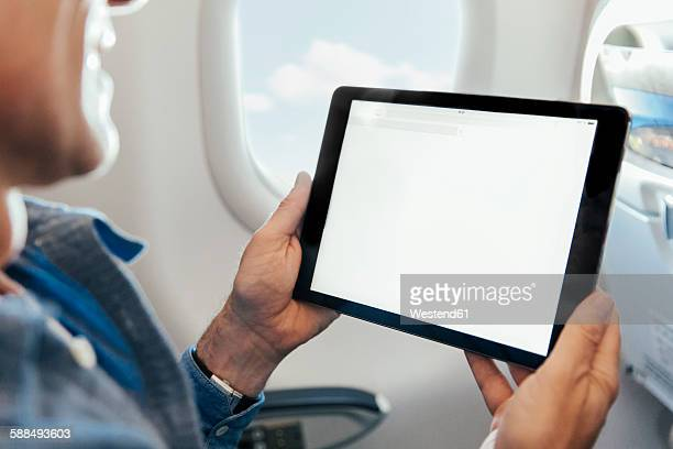 Man sitting on an airplane holding digital tablet