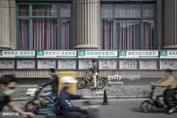 A man sitting on an ofo bike reads a newspaper in Shanghai China on Thursday May 25 2017 In China abicyclesharingphenomenon is changing the way...