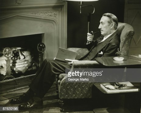 Man sitting on armchair in front of fireplace, (B&W)