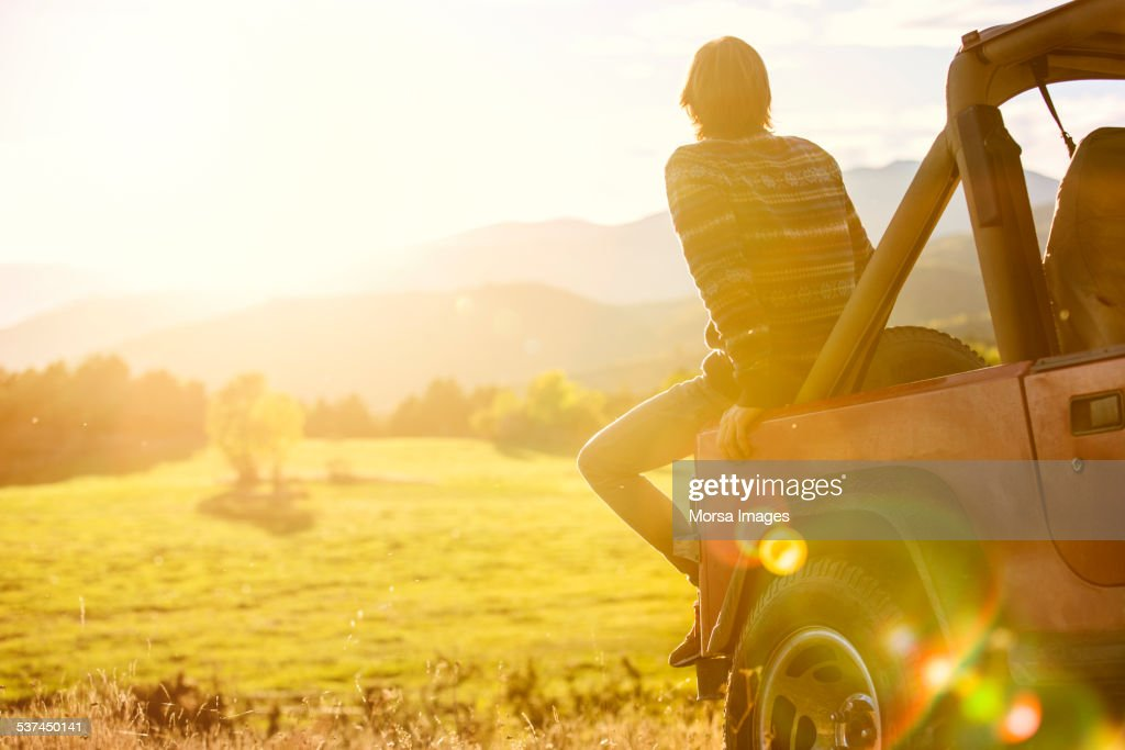 Man sitting on back of SUV parked at field : Stock Photo