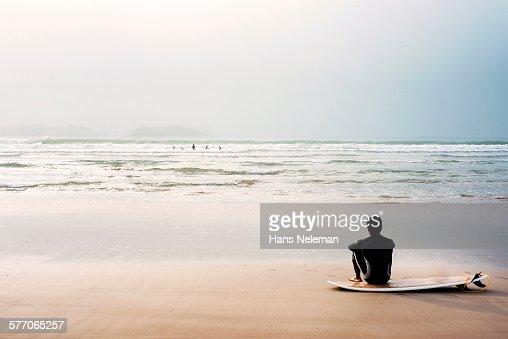 Man sitting on beach by surfboard