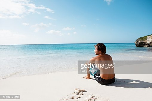 Man sitting on beach : Bildbanksbilder