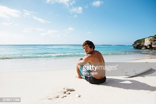 Man sitting on beach : Foto de stock