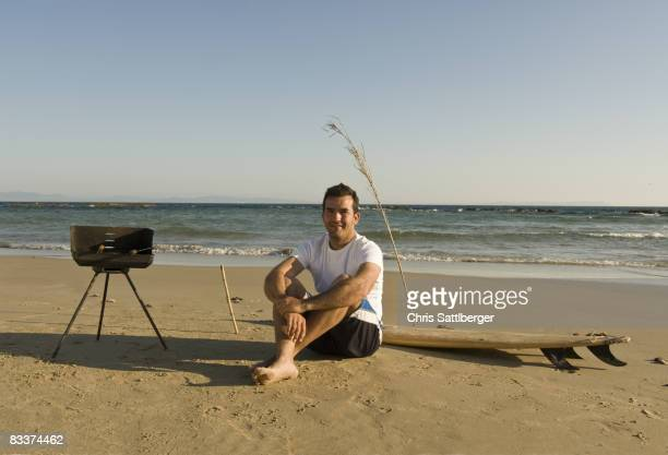 man sitting on beach with surfboard and barbecue