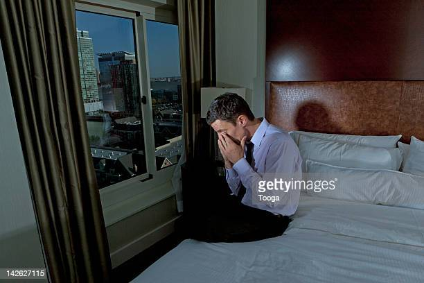 Man sitting on bed after long day at work