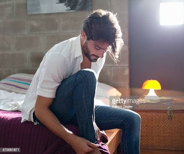 man sitting on bed, getting dressed