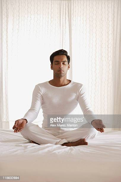 man sitting on bed in white room