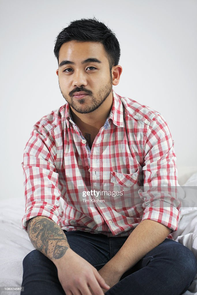 Man sitting on bed, portrait : Stock Photo
