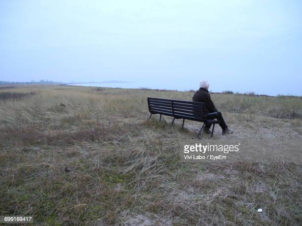 Man Sitting On Bench Against Sky