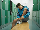 Man sitting on bench in locker room tying laces