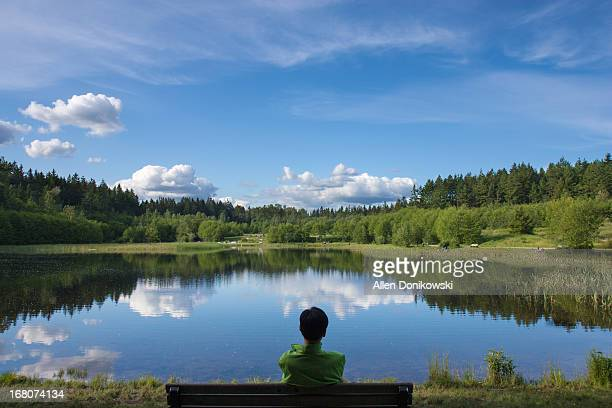 man sitting on bench looking at lake and forest