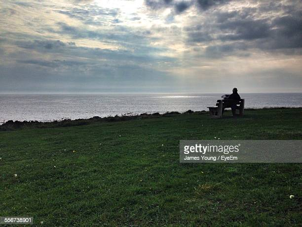 Man Sitting On Bench, Looking At Sea