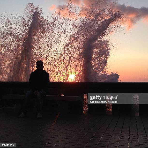Man Sitting On Bench With High Tide Splashing In Sea