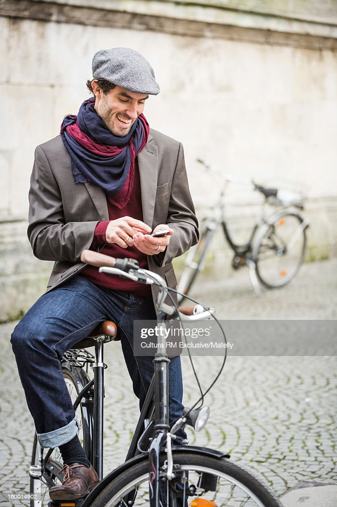 Man sitting on bicycle on city street