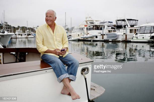 Man sitting on boat text messaging on cell phone