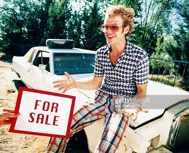 Man sitting on bonnet of car, person holding 'For Sale' sign