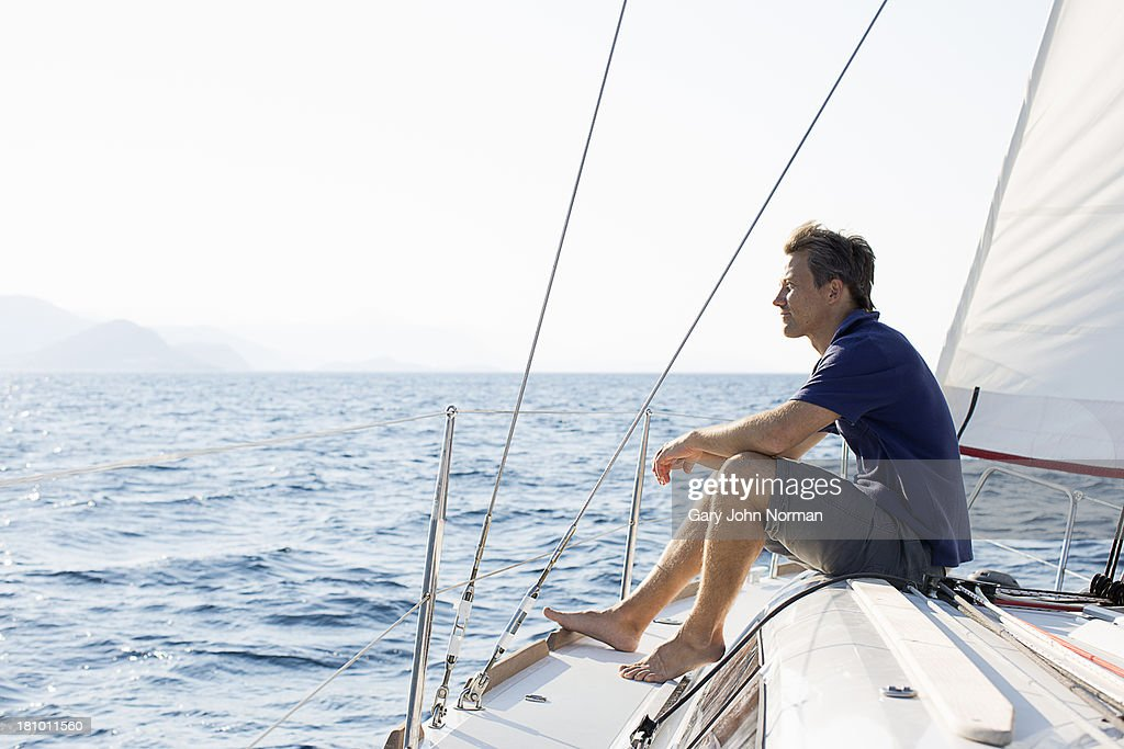 man sitting on bow of sailing yacht
