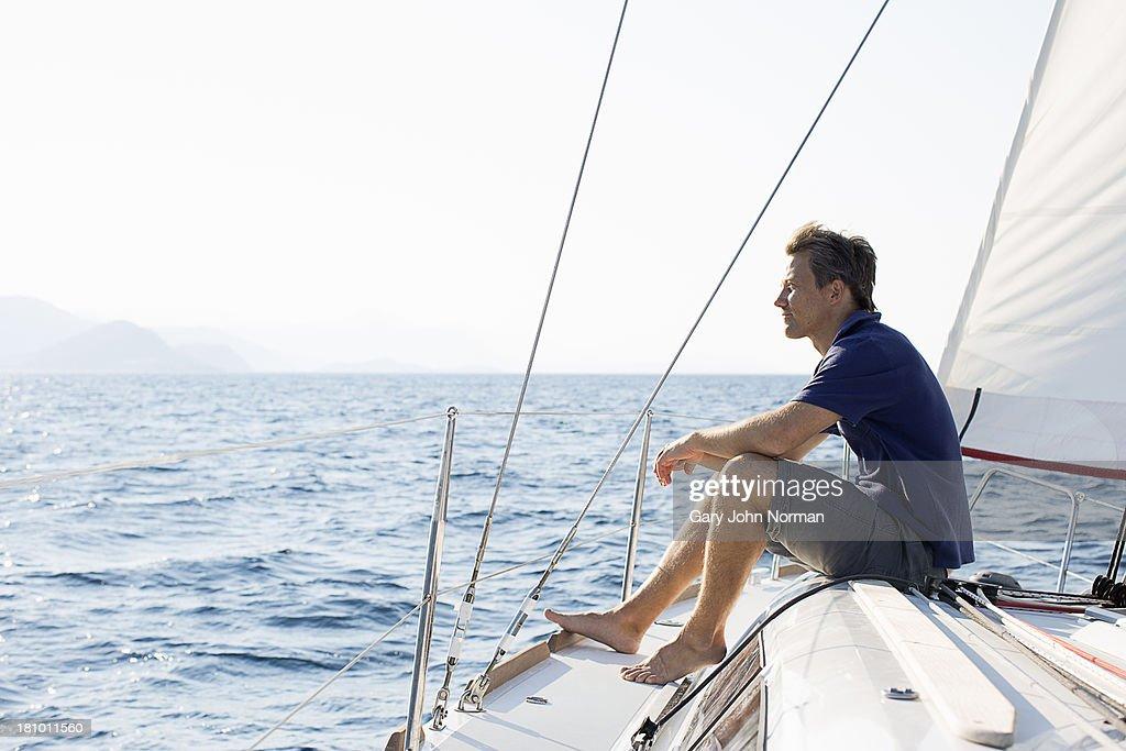 man sitting on bow of sailing yacht