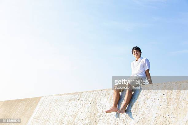 Man Sitting On Breakwater