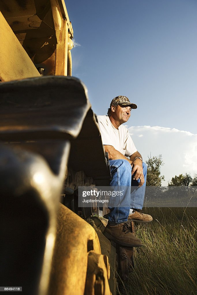 Man On Bulldozer : Man sitting on bulldozer stock photo getty images