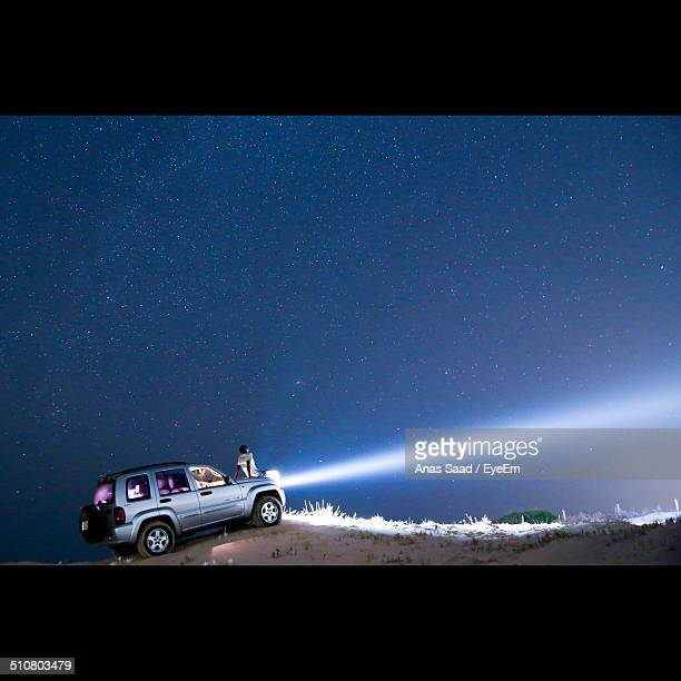 Man sitting on car at hill during night