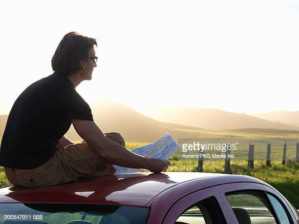 Man sitting on car roof, holding map