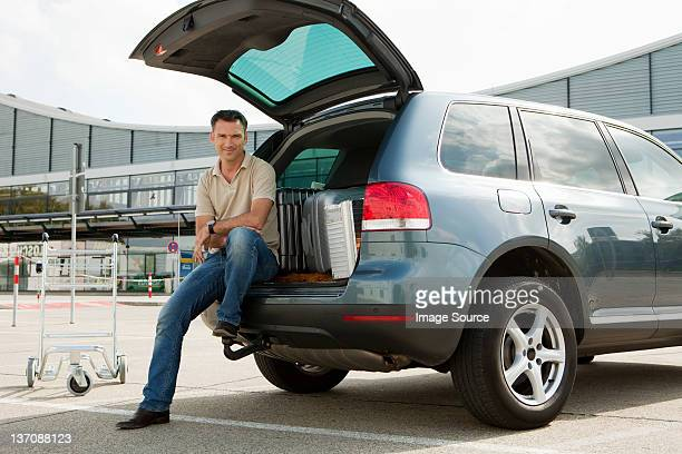 Man sitting on cart in airport carpark