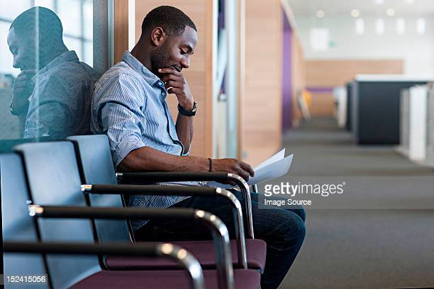 Man sitting on chair reading document