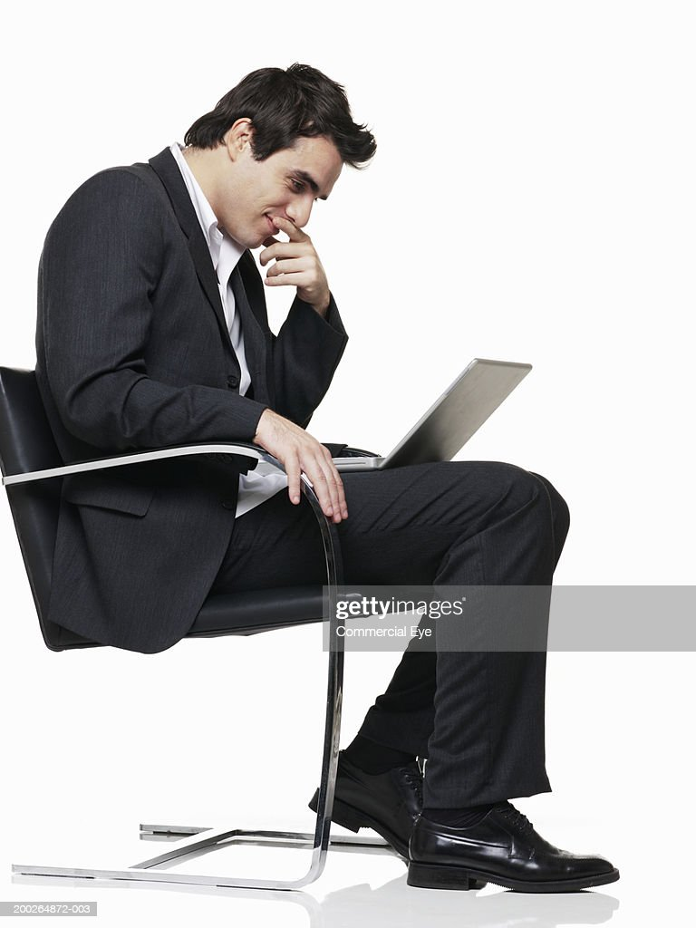 Man sitting in chair side - Man Sitting On Chair Using Laptop One Hand On Chin Side View