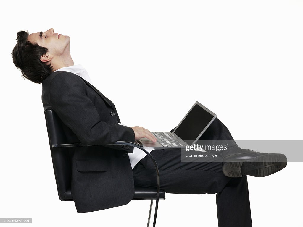 Man sitting in chair side - Man Sitting On Chair Using Laptop Side View Stock Photo
