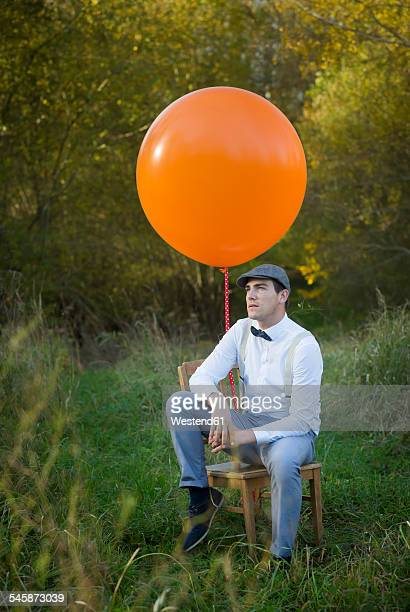 Man sitting on chair with balloon on meadow