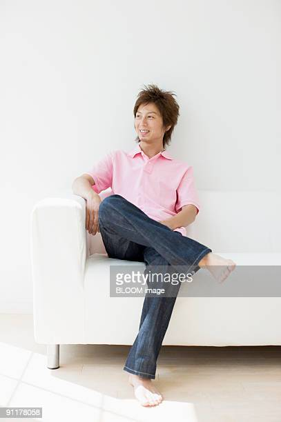Man sitting on couch, legs crossed
