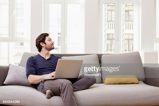 man sitting on couch using laptop stock photo getty images. Black Bedroom Furniture Sets. Home Design Ideas