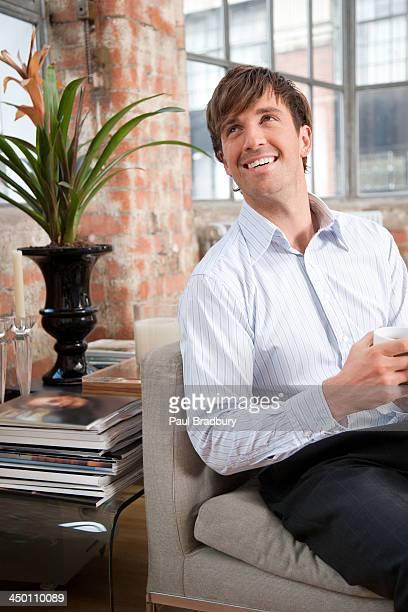Homme assis sur un canapé avec une tasse de café de la maison moderne