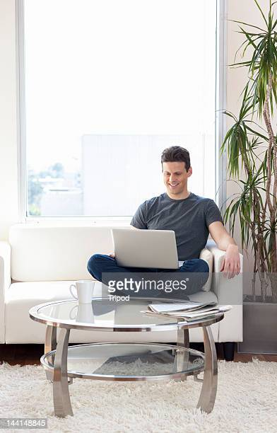 Man sitting on couch working on laptop computer