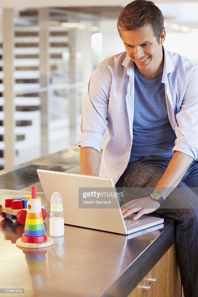 Man sitting on counter typing on laptop : Stock Photo
