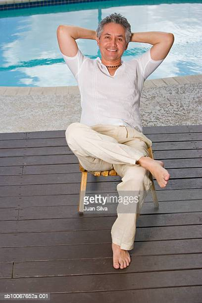 Man sitting on deck by swimming pool, portrait