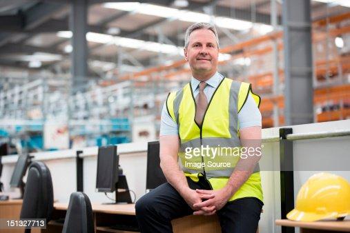 Man sitting on desk in warehouse, portrait : Stock Photo