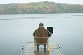 Man sitting on dock with laptop computer
