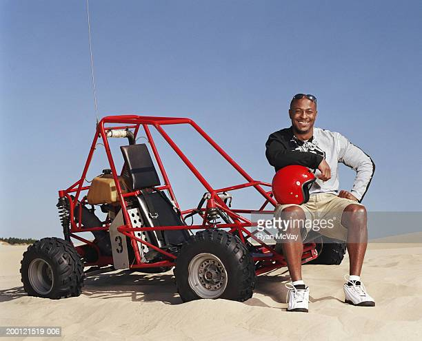 Man sitting on dune buggy, resting arm on crash helmet, portrait